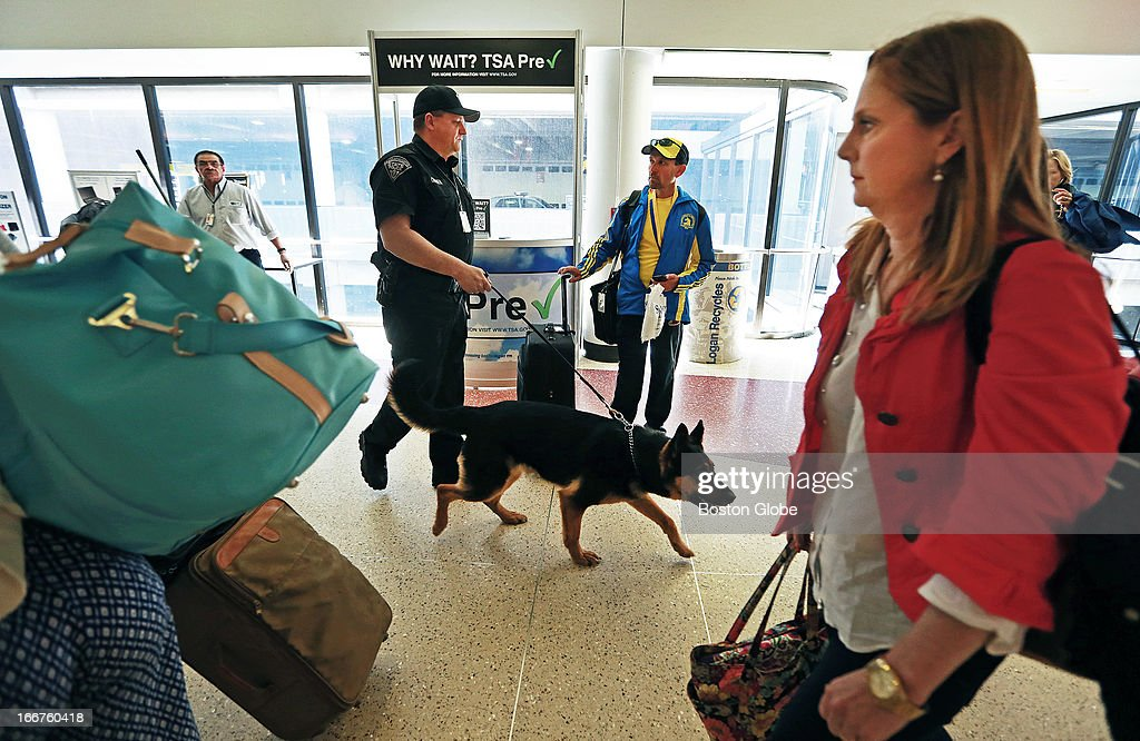 Massachusetts State Trooper Mike Currier with his dog 'Chico' as they patrol Terminal B at Logan Airport. They are walking past a man wearing a marathon jacket.