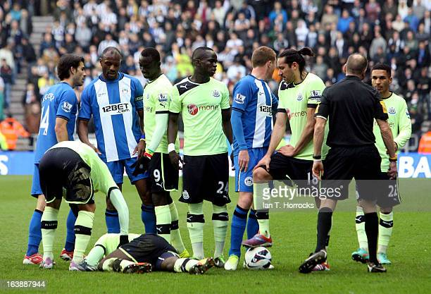 Massadio Haidara of Newcastle United lies injured during the Barclays Premier League match between Wigan Athletic and Newcastle United on March 17...