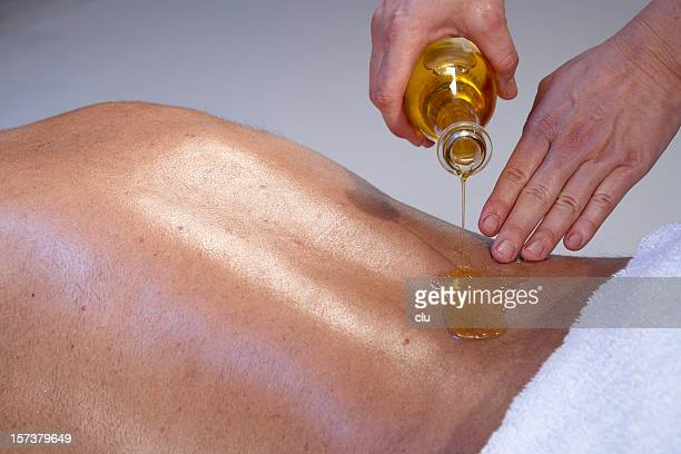 Massage for man: masseuse pouring oil on the back