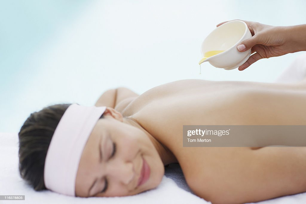 Massage oil being poured on womans back : Stock Photo