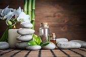 massage oil ,white zen  balance stones,orchid and bamboo leaves on the wooden table