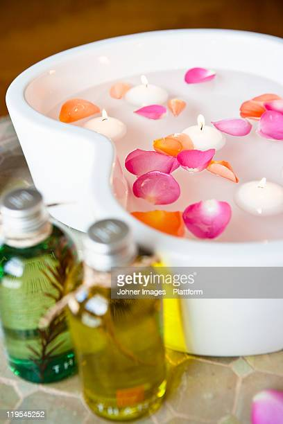 Massage oils with petals floating on water