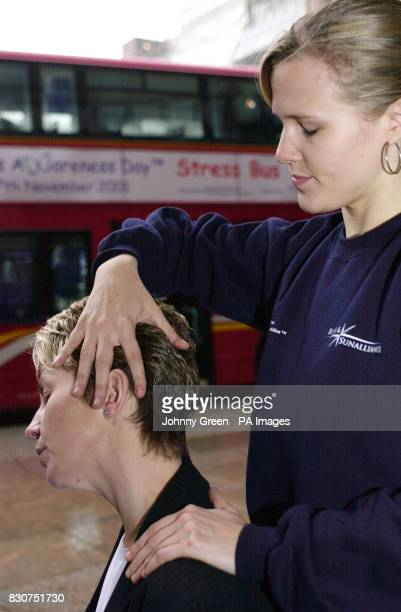 Massage Practitioner Alice Whitney from Positive Touch Ltd gives a massage to a city worker outside the Broadgate Centre London as part of National...