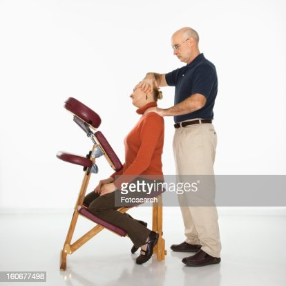 Massage therapist massaging neck of woman sitting in massage chair