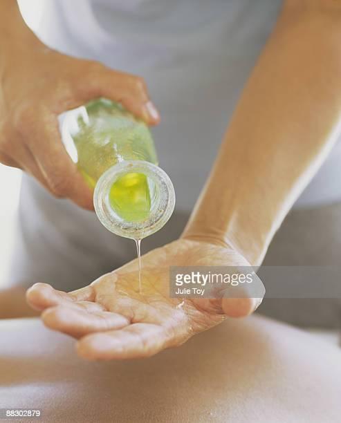 Masseur pouring liquid aloe vera into his hand