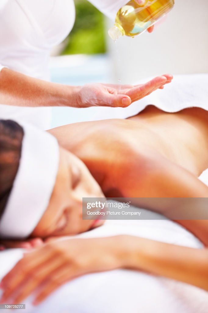 Masseuse using an oil to massage a woman's back : Stock Photo