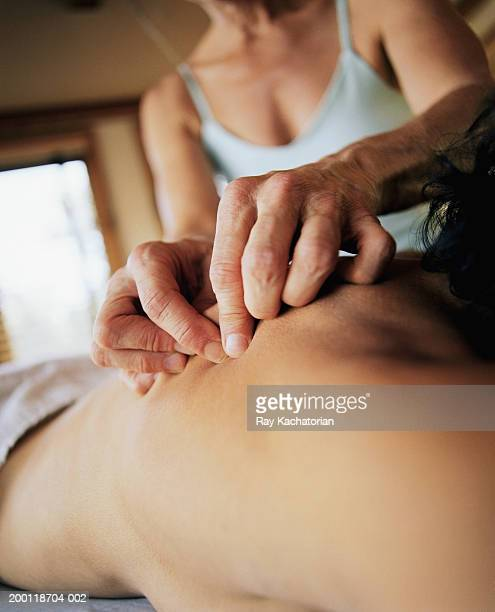 Masseuse using skin roll massage technique on woman's back