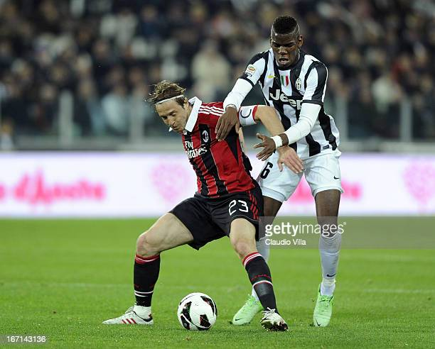 Massimo Ambrosini of AC Milan and Paul Pogba of Juventus compete for the ball during the Serie A match Juventus FC v AC Milan at Juventus Arena on...