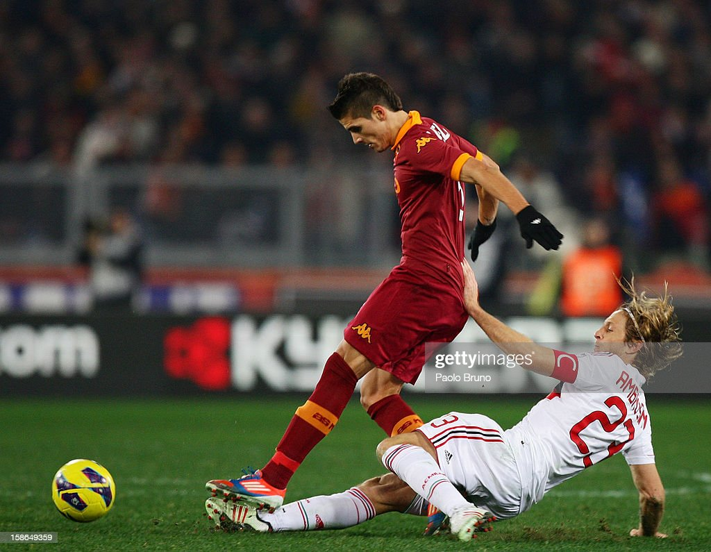 Massimo Ambrosini (R) of AC Milan competes for the ball with Erik Lamela of AS Roma during the Serie A match between AS Roma and AC Milan at Stadio Olimpico on December 22, 2012 in Rome, Italy.