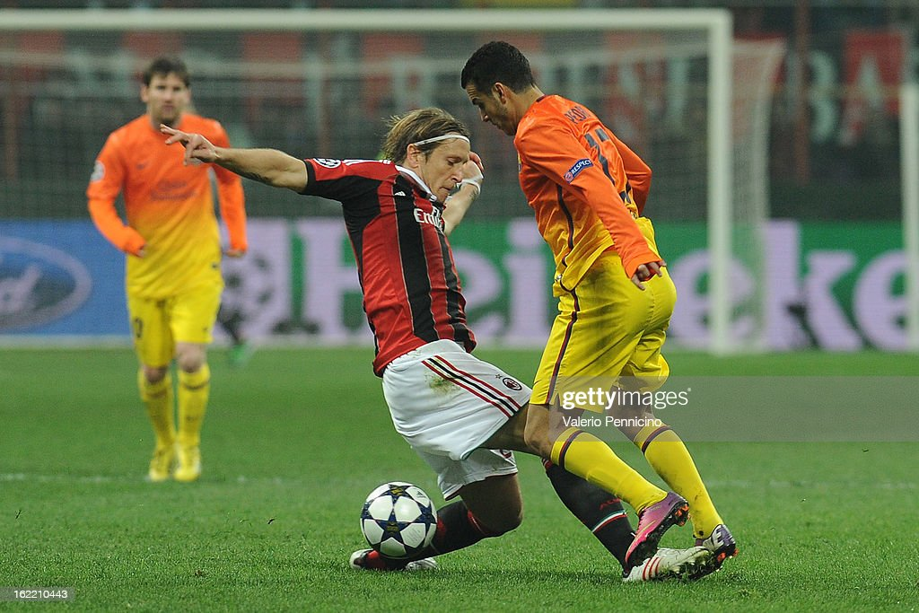 Massimo Ambrosini (L) of AC Milan tackled Pedro Rodriguez of Barcelona during the UEFA Champions League Round of 16 first leg match between AC Milan and Barcelona at San Siro Stadium on February 20, 2013 in Milan, Italy.