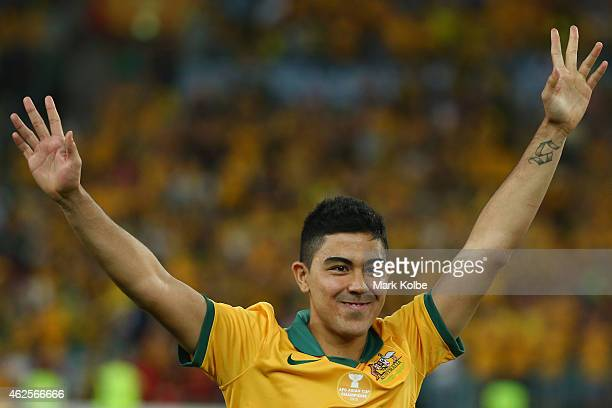 Massimo Luongo of Australia waves to the crowd as he walks to the stage to receieve the most valuable player at the 2015 Asian Cup award during the...