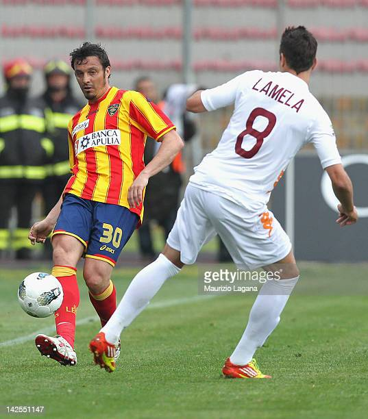 Massimo Oddo of Lecce is challenged by Eric Lamela of Roma during the Serie A match between US Lecce and AS Roma at Stadio Via del Mare on April 7...