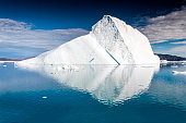 An iceberg is a large piece of freshwater ice that has broken off a glacier or an ice shelf and is floating freely in open water. It may subsequently become frozen into pack ice (one form of sea ice).