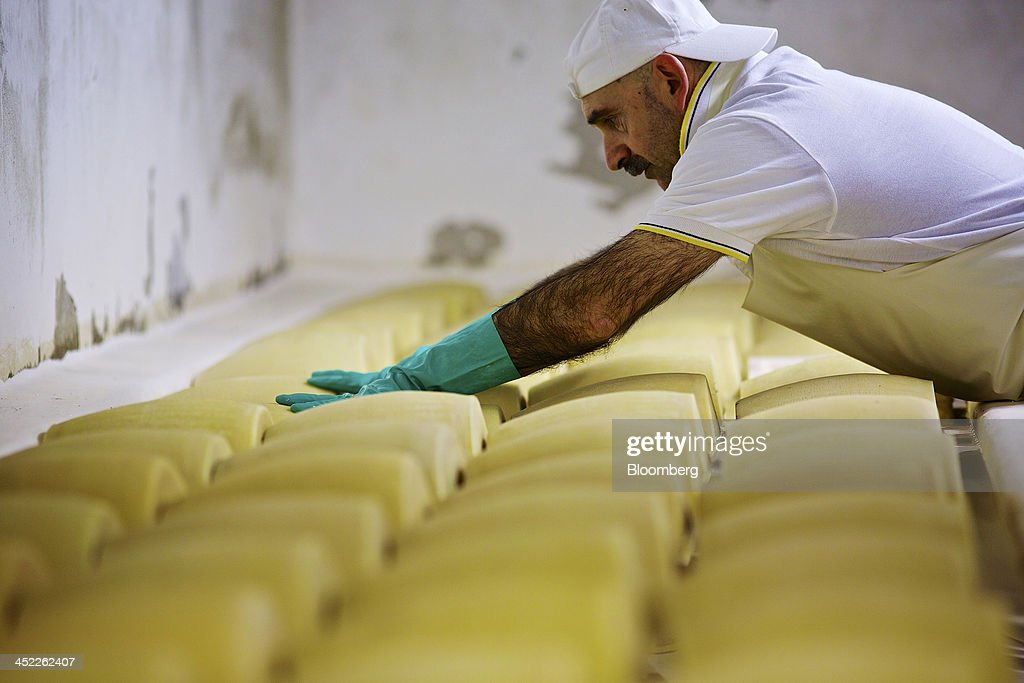 A master cheese maker checks whole cheeses during the salting process of Parmigiano Reggiano manufacturing at Il Trionfo cheese makers in San Secondo Parmense, Italy, on Tuesday, Nov. 26, 2013. Italian borrowing costs dropped at an auction of six-month bills as investors await signals from the European Central Bank about further stimulus. Photographer: Gianluca Colla/Bloomberg via Getty Images