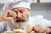 Master chef cutting onion with tears in his eyes