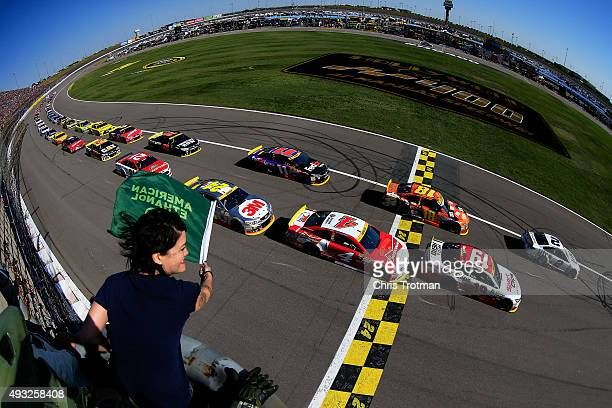 Master Chief Kiki Wolfkill waves the green flag as Brad Keselowski driver of the Miller Lite Ford leads the field past the green flag to start the...