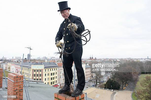 Master chimneysweep Norbert Skrobek demonstrates his trade using a coiledwire brush on a rooftop in Berlin's Kreuzberg district December 27 2012 A...
