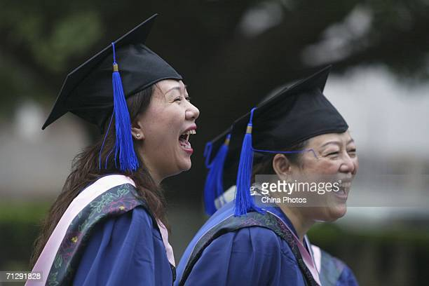 Master graduates laugh as they pose for pictures at Peking University on June 24 2006 in Beijing China China will see 413 million college graduates...