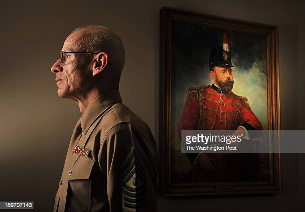 Master Gunnery Sgt D Michael Ressler historian with 'The President's Own' United States Marine Band poses for a portrait near a painting of John...