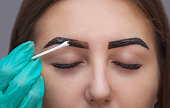 Master corrects makeup, it gives shape and color the eyebrows henna in a beauty salon, Spa. Professional skin care.