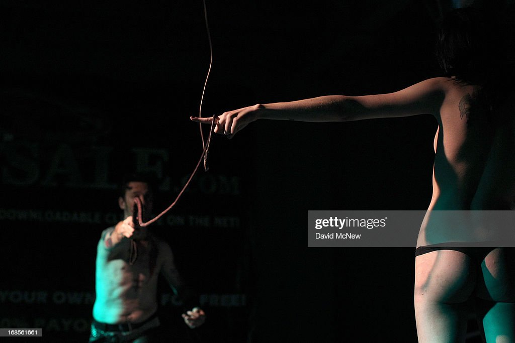 Master Nik wraps a whip around the finger of a voluntarily submissive woman at a dungeon party during the domination convention, DomCon LA, in the early morning hours of May 11, 2013 in Los Angeles, California. The annual convention was started in 2003 by fetish professional Mistress Cyan to bring together enthusiasts of BDSM (Bondage, Discipline, Submission and Dominance) and other fetishes.