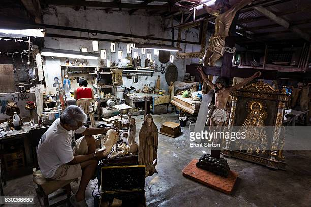 Master sculptor Marcial Bernales carves an Ivory head and hand set for a Catholic religious icon in his workshop in Valenzuela close to Manila...