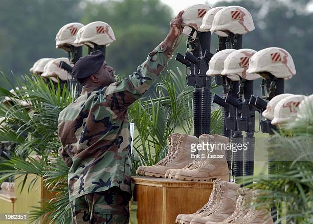 Master Sgt Herman Lovett removes dog tags and helmet IDs from fallen soldiers' helmets during a memorial service April 30 2003 at Fort Stewart...
