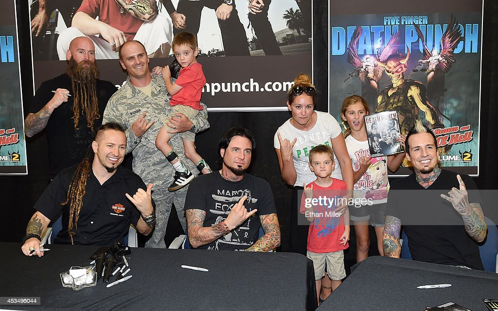 Master Sgt. Todd Badger (3rd L) and members of his family pose with bassist Chris Kael (L), guitarist Zoltan Bathory (2nd L), guitarist Jason Hook (5th L) and drummer Jeremy Spencer (R) of Five Finger Death Punch at Nellis Air Force Base as the band highlights its campaign to raise awareness about veterans suffering from post-traumatic stress disorder (PTSD), in part by launching the video 'Wrong Side of Heaven,' that deals with the subject on August 11, 2014 in Las Vegas, Nevada.