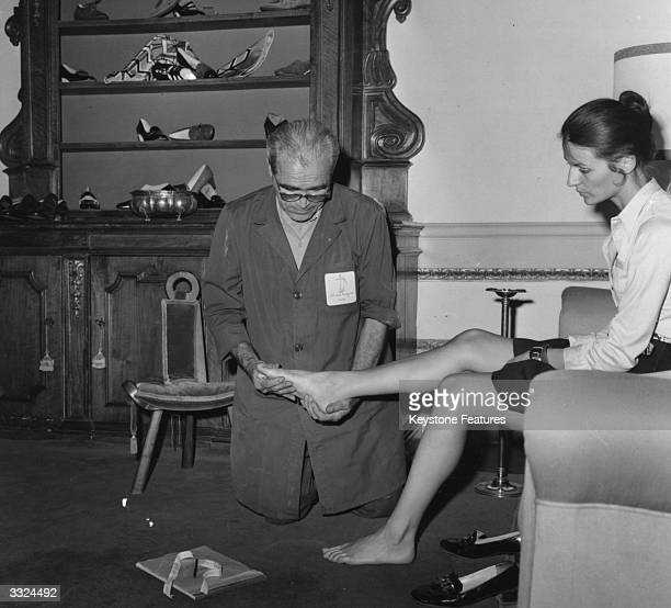 Master shoemaker Gino Becucci of the Italian shoemaking Ferragamo family measures the feet of a client in Florence