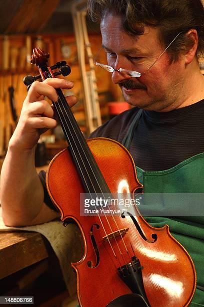 Master violin maker checking violin in his workshop.