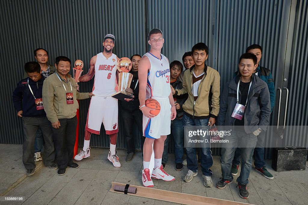 MasterCard Center arena workers gather near lifesize cutouts of LeBron James of the Miami Heat and Blake Griffin of the Los Angeles Clippers during...