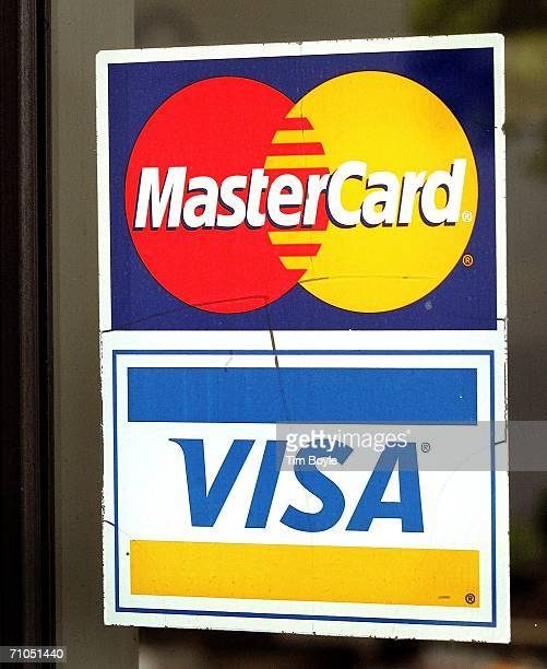MasterCard sticker above a Visa card sticker is seen on a glass window of a store May 25 2006 at its store in Niles Illinois MasterCard shares were...