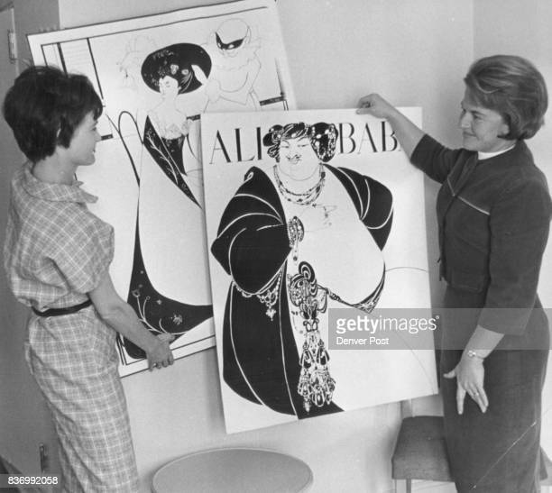 Masterminding black and white decor for Feb 12 Junior League Ball is Mrs Joseph Obering left who displays artnouveau placards to Mrs William Berge...