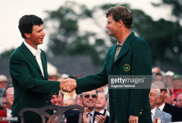 Masters Champion Larry Mize shakes hands with 1988 Masters Champion Sandy Lyle at the Presentation Ceremony during the 1988 Masters Tournament at...