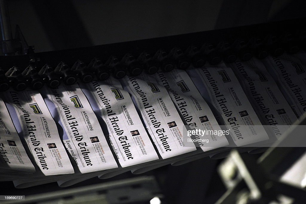 Mastheads are seen on newly-printed editions of the International Herald Tribune newspaper on a conveyor belt at the Kathimerini printing plant in Paiania, Greece, on Thursday, Jan. 17, 2013. An anarchist group claimed responsibility for a series of attacks early on Jan. 11 when unidentified perpetrators threw makeshift bombs made from propane gas canisters into the homes of five Greek journalists working for national media saying it was to protest coverage of the country's financial crisis seen as sympathetic to the government. Photographer: Kostas Tsironis/Bloomberg via Getty Images