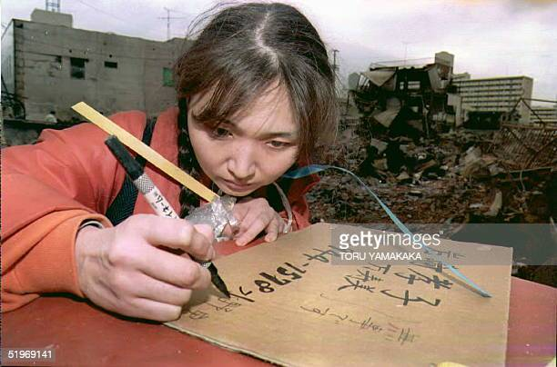 Masumi Iwasaki prints a cardboard sign bearing her new telephone number and address before posting the sign in her destroyed Nagata neighborhood 23...