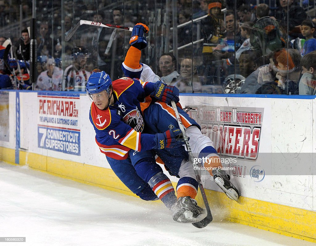 Mat Clark #2 of the Norfolk Admirals checks John Persson #23 of the Bridgeport Sound Tigers during an American Hockey League game on February 2, 2013 at the Webster Bank Arena at Harbor Yard in Bridgeport, Connecticut.