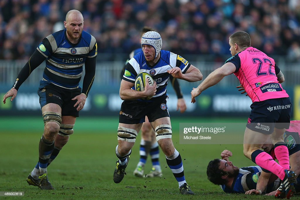 Mat Gilbert (C) of Bath looks to break as Gavin Evans (R) of Cardiff Blues closes in during the LV Cup match between Bath and Cardiff Blues at the Recreation Ground on January 25, 2014 in Bath, England.