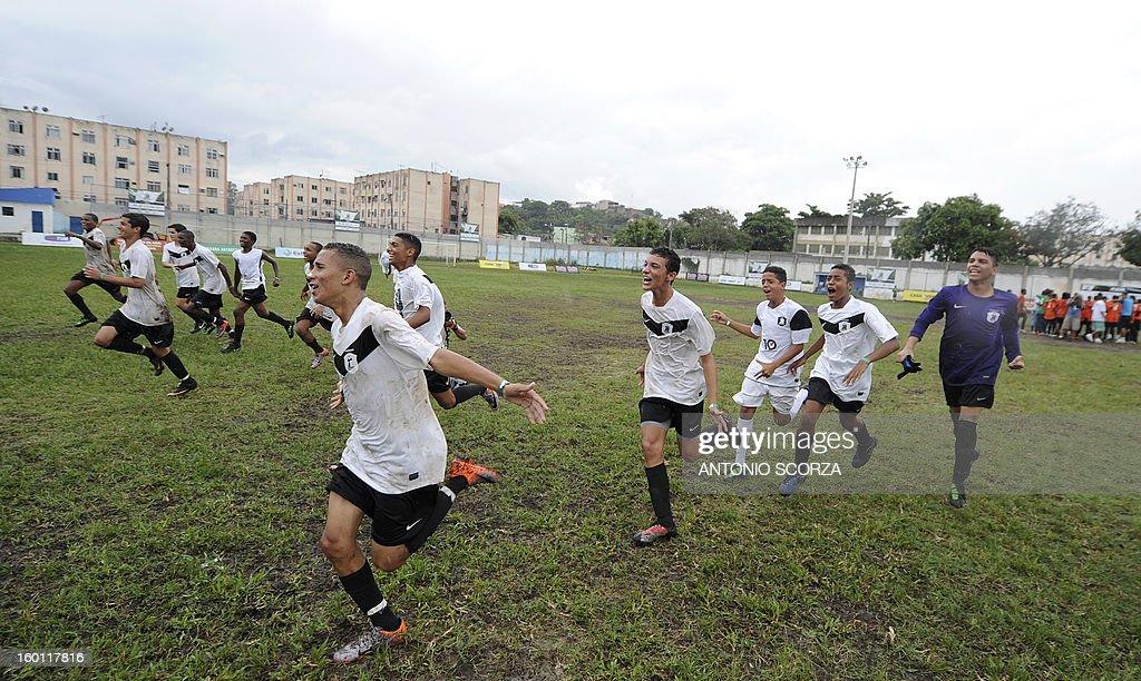 Mata Machado players celebrate after defeating Complexo da Penha 1-0 for their Favelas Football Cup semifinal football match in Bangu, 65 kms from Rio de Janeiro, Brazil, on January 26, 2013. AFP PHOTO/ANTONIO SCORZA