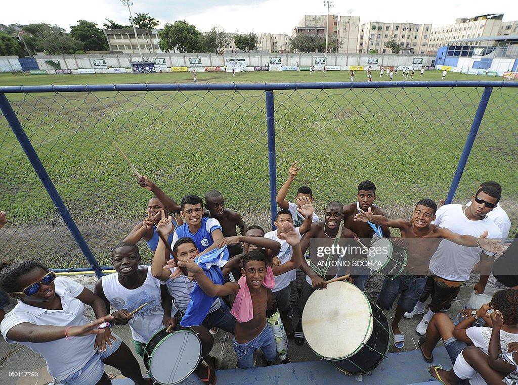 Mata Machado supporters cheer for their team during their Favelas Football Cup semifinal football match against Complexo da Penha in Bangu, 65 kms from Rio de Janeiro, Brazil, on January 26, 2013. AFP PHOTO