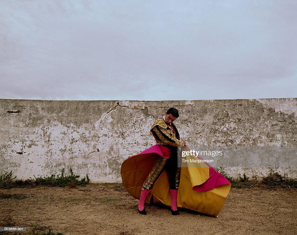 Matador swinging cloak in arena, portrait : Stock Photo