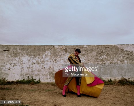 Matador swinging cloak in arena, portrait