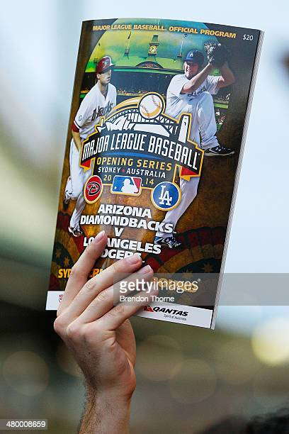 Match day programs are held up for sale during the opening match of the MLB season between the Los Angeles Dodgers and the Arizona Diamondbacks at...