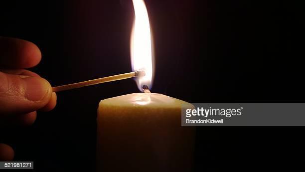 Match lighting candle in dark