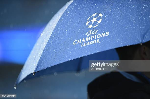A match official shelters under an umbrella as heavy rain continues to pour ahead of the UEFA Champions League group C football match between...