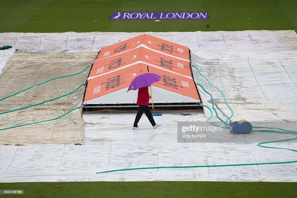 A match official walks across a covered pitch as rain forces the match to be called off in the third one day international (ODI) cricket match between England and Sri Lanka at Bristol cricket ground in Bristol, south-west England, on June 26, 2016. / AFP / JON
