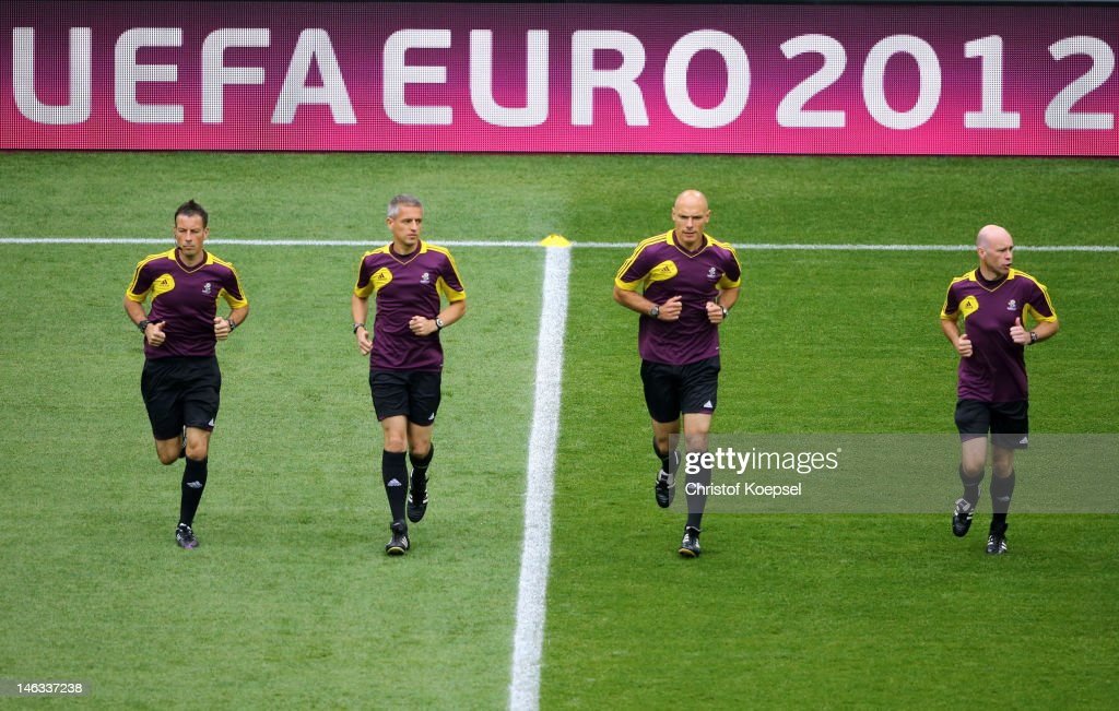 Match officials, additional assistant referee Mark Clattenburg and assistant Peter Kirkup, referee Howard Webb, assistant referee Michael Mullarkey warm up ahead of the UEFA EURO 2012 group C match between Italy and Croatia at The Municipal Stadium on June 14, 2012 in Poznan, Poland.