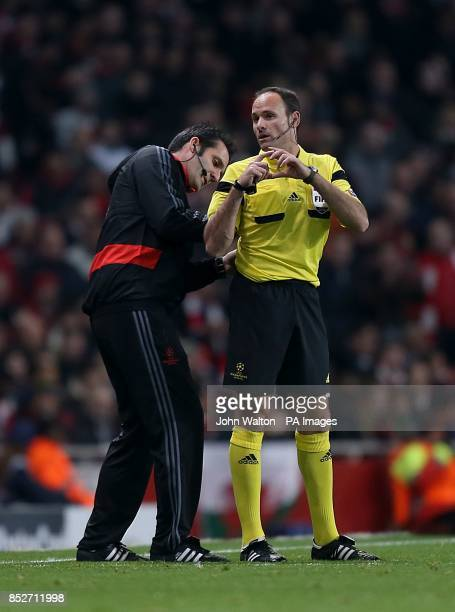 Match referee Antonio Miguel Mateu Lahoz gets his microphone fixed on the touchline