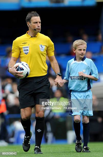 Match referee Mark Clattenburg walks out onto the pitch before kickoff with a mascot