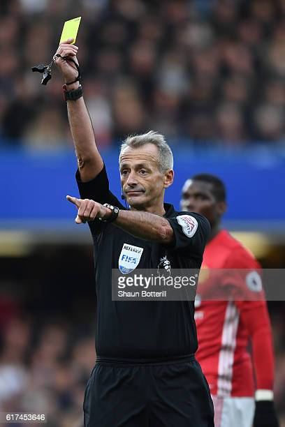 Match Referee Martin Atkinson shows a yellow card during the Premier League match between Chelsea and Manchester United at Stamford Bridge on October...